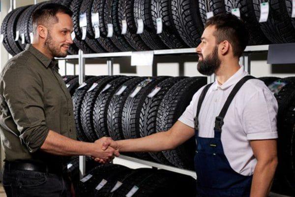 04 - mecanico-de-reparos-confiante-apertando-a-mao-do-cliente-vendedor-ajudando-na-escolha-do-pneu-na-oficina_183219-6169